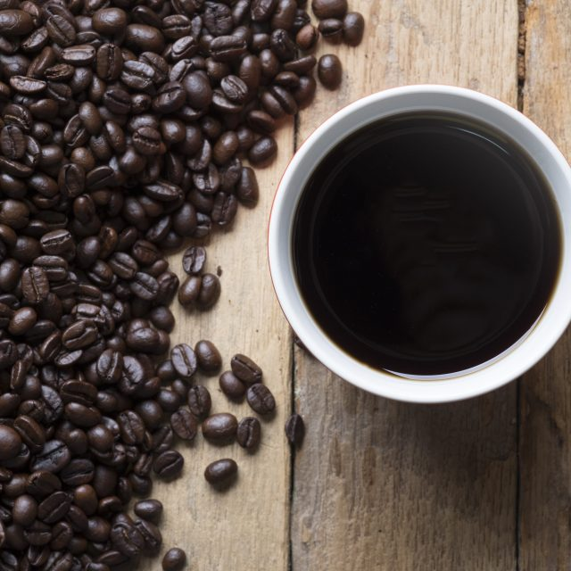 topview of the red cup of coffee and coffee beans