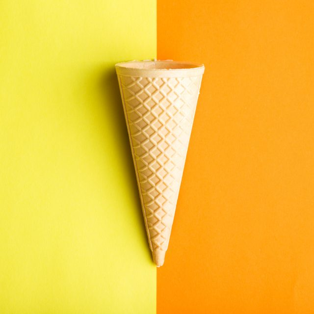 Ice cream cone on double colorful background.
