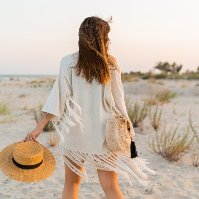 Summer mood. Playful brunette woman dancing in sunlight on the beach. Boho style. Trendy necklase and earrings.  View from back.